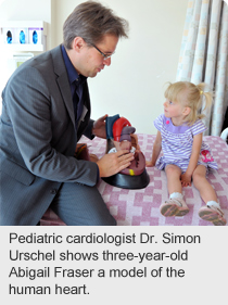 Pediatric cardiologist Dr. Simon Urschel shows three-year-old Abigail Fraser a model of the human heart.