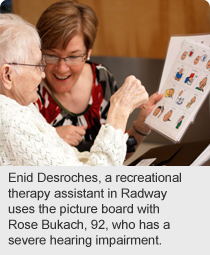Enid Desroches, a recreational therapy assistant in Radway uses the picture board with Rose Bukach, 92, who has a severe hearing impairment.