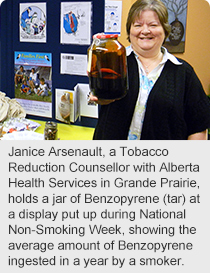 Janice Arsenault, a Tobacco Reduction Counsellor with Alberta Health Services in Grande Prairie, holds a jar of Benzopyrene (tar) at a display put up during National Non-Smoking Week, showing the average amount of Benzopyrene ingested in a year by a smoker.