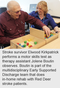 Stroke survivor Elwood Kirkpatrick performs a motor skills test as therapy assistant Jolene Boutin observes.