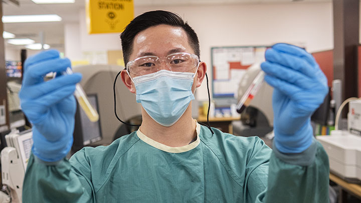 Alberta Precision Laboratories medical lab technologist Steven Dang shows the difference between normal blood plasma (left), and plasma from a patient treated with hydroxocobalamin for cyanide poisoning (right).