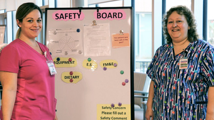 Health Care Aides Nicole Woods, left, and JoAnne Derouard pose by a patient safety board that shares safety news and invites comments from frontline staff on how to further improve safety at Edson Continuing Care Centre.