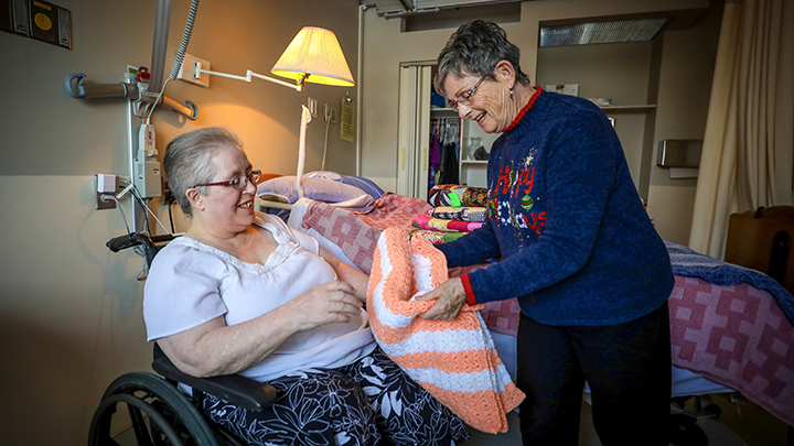 Vicki Shultz, left, was delighted to receive a quilt from Pat Grenier. Shultz and 29 other residents in long-term care at the Innisfail Health Centre received the homemade quilts as Christmas gifts thanks to the sewing talent and generosity of Grenier. Photo by Leah Hennel