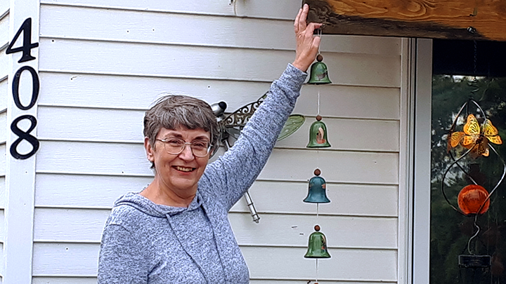 Research study participant Michelle Archibald hangs some homemade wind chimes while enjoying full range of motion in her left arm after recovering from elbow surgery.