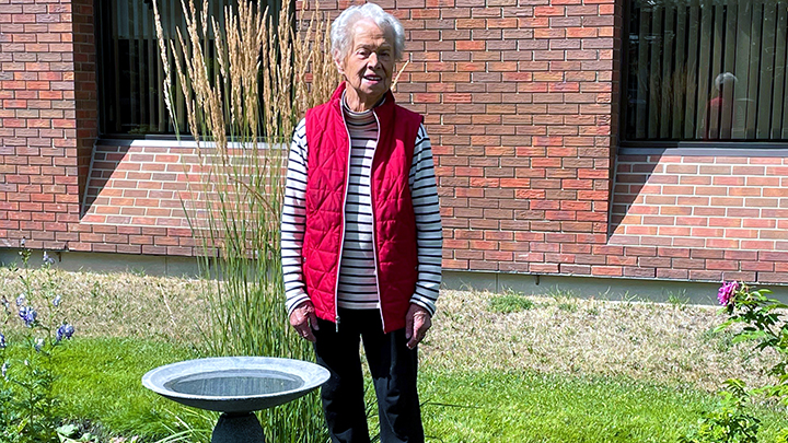 Pat Grayling, a long-time AHS volunteer, poses next to the garden named in her honour.