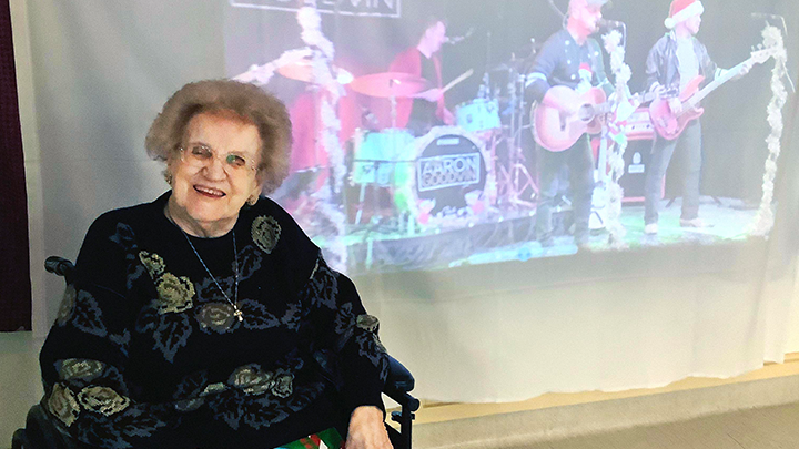 Anne Wrona enjoys some 'screen time' with country music star Aaron Goodvin at a virtual concert arranged for continuing care residents at Milk River Health Centre. Other performers included Duane Steele and Bobby Wills.