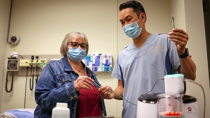 Brenda Crowell, left, was the first patient in Canada to undergo an embolectomy using the new CAT12 Lightning catheter as demonstrated by interventional radiologist Dr. Jason Wong. Dr. Wong and his team saved Brenda's life with the device after she developed deadly blood clots from a COVID-19 infection in May, 2021.