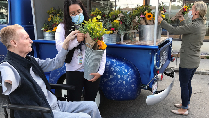 Mackenzie Place resident Darwin Tost gets some assistance from recreation therapist Gina Mariano in choosing a bouquet from Joline Willsey's Gypsy Blooms Flower Truck in Grande Prairie.