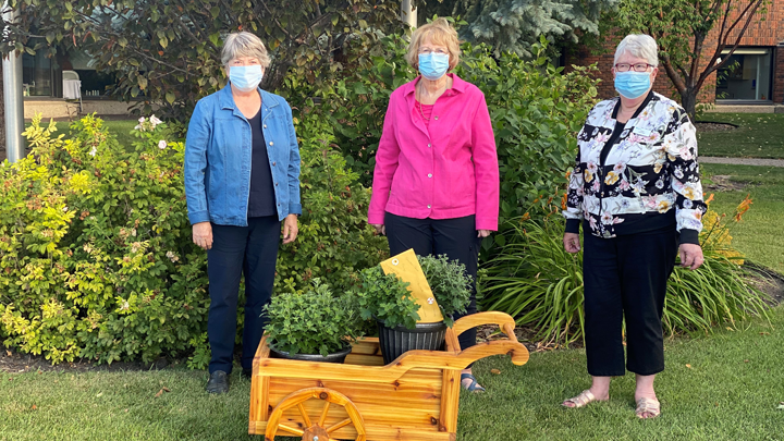 Members of the Auxiliary to the Lacombe Hospital and Care Centre — from left, Marianne Gustafson, president, Kathy Medd, treasurer and Dawn Atkinson, vice president — pose with a handcrafted cedar cart made by local resident Don Gustafson for the winner of the group's annual raffle.