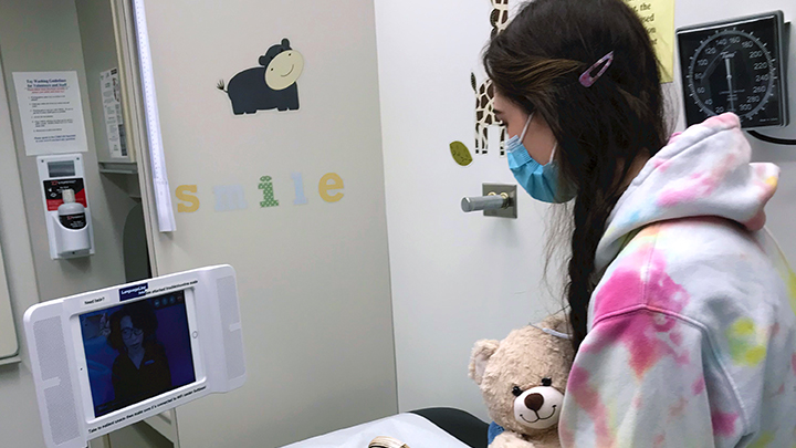 A young patient makes use a video link and an interpreter to ask questions about her health.