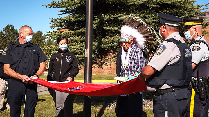 Siksika Nation elder Clement Leather says a prayer over the Siksika Nation flag before it is raised at Strathmore District Health Services.