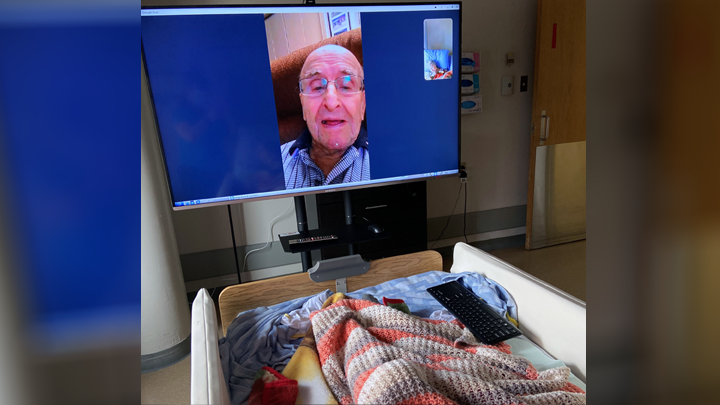 Paul Routhier, 92, enjoys a virtual visit with his wife, Lorraine (not shown), a continuing care resident at the St. Therese - St. Paul Healthcare Centre, thanks to a new 55-inch smart TV donated by Family and Community Support Services.